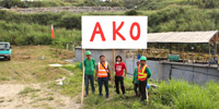 Four guys are standing along with the sign AKO.