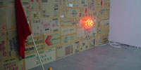A orange color neon sign that can be read But in Japanese on the wall.